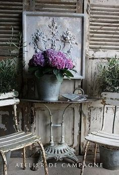 Shabby Chic Outdoors, Old Table, Chairs, pink Flowers with Hanging Bas Relief Sculpture, Atelier de campagne
