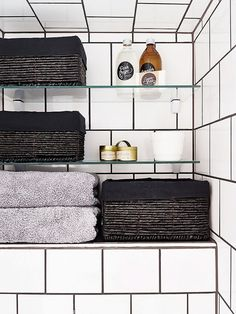 Minimalist bathroom with square ceramic tile, dark grout, a built-in shelf styled with luxe towels