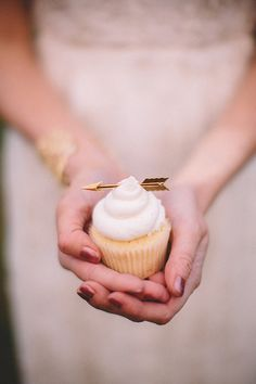 White cupcakes with frosting and golden arrow cake topper