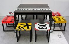 Recycled table with inset signage stripe. Folded road sign stools.