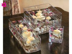 Cristalería geométrica con velas flotantes para el centro de mesa de tu boda.