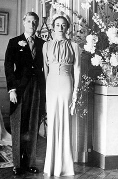 "Wallis Simpson and Edward wed  3 June 1937  Wallis wore a nipped-at-the-waist dress created by Mainbocher in what was termed her signature colour of ""Wallis blue"" reportedly to match her eyes. Her co-ordinating blue straw hat, by Caroline Reboux, had a halo effect with pale blue tulle and her matching gloves were created from the same blue silk crepe as her dress.["