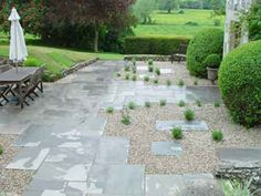 White of Witchampton - landscape gardener - A grey natural stone paving laid in a semi random pattern with gravel and planting.