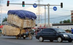 A man rides an overloaded motor tricycle on a busy street in Beijing