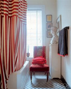 """In the New York City apartment shared by Tom Bezucha and Margaret """"Sam"""" Hamilton, a lively red-and-white-striped shower curtain and striped terry towels make a brilliant statement in a bathroom. - ELLEDecor.com"""