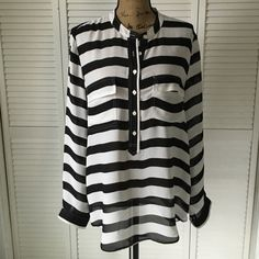 Striped Blouse Black and white striped blouse. Collarless. A few loose threads around the buttons and hems, which I have found is typical for this material, but still in excellent condition. Only worn once. Baggy L so it could easily fit an XL. Banana Republic Tops Blouses