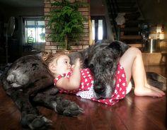niña jugando con perrito negro