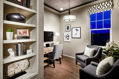 This contemporary home office features a geometric patterned valance, drum pendant light, computer desk, and open shelving for storage and display.