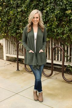 We've already made up our minds about this cardigan- it's a must have! Chunky knit textured cardigan in a smokey olive and two front pockets. More fabric draped in the front for added detail. Proudly
