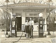 A husband and wife stand outside their Standard Oil, Red Crown/White Crown Gas Service Station....