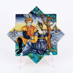 <p>This+hand+painted+ceramic+wall+and+floor+tile+depicts+a+scene+of+Courtly+Love.<br+/>The+style+of+the+mural+is+the+<a+href='http://www.thatsarte.com/0/history-and-tradition#a4'>istoriato</a>+that+originated+during+the+Italian+Renaissance.+Its+subjects+were+executed+with+a+realism+quite+unlike+any+previous+pottery+decoration+and+nowadays+they+are+much+sought+after+collector+items.+<br+/>Niccacci's+handmade+tiles+are+available+in+different+sizes+and+shapes+to+fulfill+any+and+all+condit...