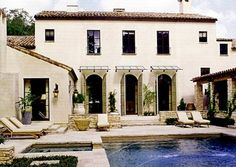 Glass and metal frame awnings above arched french doors are lovely!