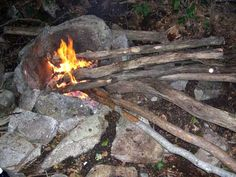 "A ""Lazy Man"" fire with a nice 3-sided stone fire pit, and a high back to reflect light and heat back into camp."