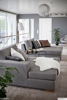 sohva,makuuhuone,oleskelutila,vaaleat sävyt,sisustustyynyt,olohuone,sohvaryhmä,divaani,harmaa,maalattu seinä,talja,sivupöytä,sohvapöytä,kori...