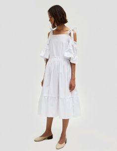 Feminine dress from Farrow in White. Square neckline. Thin straps with tie adjustment. Shoulder cutouts. Short flounce sleeves. Waisted. Concealed side zip closure. Full skirt with ruffle detail at hem. Lined. Mid length.  • Cotton Poplin • 100% cotton