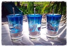 Set of 3- Cute gel candles in shot glasses. Made with an assortment of seashells and natural puka sand. Ocean Blue Color Shown in Photo.