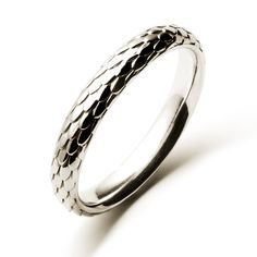 The Drake ring is detailed with beautifully engraved scales like those of a giant serpent. The band is a 3.8mm wide comfort fit and is pictured here in white gold.