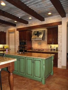 The use of distressed tin for the ceiling along with the wood beams help give this kitchen a unique rustic look while keeping some more of the modern features as well.