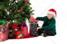 cute boy opening his christmas gift. - Portrait of a cute boy opening his christmas gift while sitting besides christmas tree, Model: Josh Chapman
