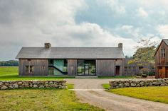 At Grey Barn Farm, a working organic farm on Martha's Vineyard, the family residence was designed by Mark A. Hutker to look like a 19th-century barn that had been repurposed for modern use.