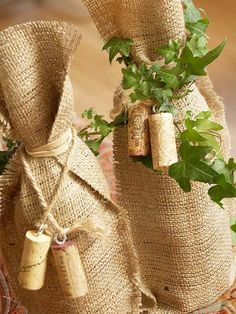 Simply Sophisticated Wine Wrap ~ A touch of green on the wine wrap instantly transforms a plain jute bag into a seasonal decoration. Wrap the wine in the bag and hold closed with a rubber band. Insert eye hooks into corks and tie them on a piece of twine to add wine accents to the bag. Ivy wrapped around the neck is a beautiful finish.