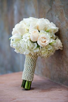 Flowers White Wedding Flowers---LOVE the pearls/beads around the bouquet.  For the 'tossing' bouquet, ask your florist to make a small version with shorter stems and white beads.