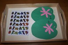Counting frog stickers onto numbered lily pads
