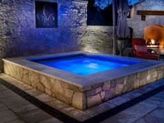 An outdoor patio becomes an architectural gem in this design from  Platinum Poolcare  that features a spa with walls of Oakfield Flagstone and a pool deck of Silver Creek Travertine with Unilock Copthorn Accent banding.