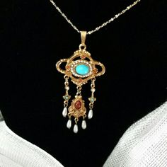 Beautiful necklace. Coral and turquoise colors accentuate the beautiful gold tone metal pendent with dangling pearl accents.  24 inch gold tone necklace.  Signed ART and is in great condition. Vintage Jewelry Necklaces