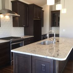Gourmet kitchen features Colonial White granite, Espresso maple cabinets with crown molding, vent hood & Sharp drawer microwave.