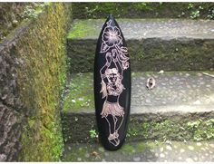 Here is a hand carved surfboard featuring a Hula dancer.    This great piece of handicraft measures 24 inches long by 6 inches wide (60 cm X 16 cm).  Great gift idea!  Perfect for your Tiki home decoration or your surfing accent room!