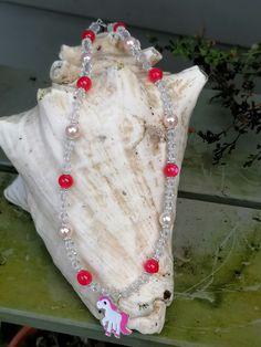 """Für kleine Einhornfans präsentiert sich hier die 42cm lange Mädchen Halskette """"Awesome"""" gefertigt mit durchsichtigen facettierten Acrylperlen, rosa Glanzperlen, pinken Acrylperlen und feinen silbernen Blumenrondellen. Als Anhänger zeigt sich ein 2cm grosses schmuckes Einhorn in pinkweiss emailliert. Girls, Crochet Necklace, Pink, Jewelry, Fashion, Unicorn, Flowers, Schmuck, Gifts"""