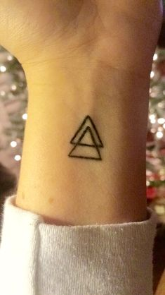 My 2nd Tattoo (on left wrist) Mother-Daughter Tattoo with triangles representing the geometric symbol for a positive change. With a point pointed upward it represents a strong foundation or stability as it is rooted into the ground as a solid base. The three sides most commonly represent Past (change) Present (strength) Future (stability) We each got two; one to represent me - and another to represent my mom, the strongest person I know. July 2014