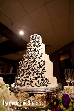 purple themed wedding, beautiful 5 tier white wedding cake with black accent on one half.