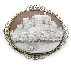 A Victorian shell cameo brooch.  The oval cameo carved to depict Edinburgh Castle, to a scrolling frame, mounted in gold, width 60mm, stamped 9ct [Amazing carving this]