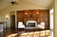 Elegant white fireplace with matching chairs, built-in cabinetry, by Hackbarth Builders in East Troy, WI
