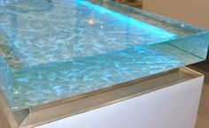"This counter top is wild--Ocean-inspired 4"" glass countertop designed to look like glistening shallow waters. LED lights embedded inside the glass."