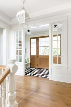 A Classic Farmhouse Meets Chic Furnishings. Love this idea for a vestibule cross mudroom einrichten A Classic Farmhouse Meets Chic Furnishings Stained Front Door, Farmhouse Stairs, Modern Farmhouse, Entryway Flooring, Tile Entryway, Checkered Floors, Entrance Foyer, Entrance Halls, Hallway Designs