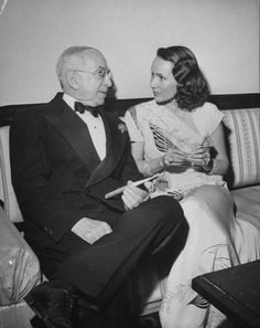 Movie producer Louis B. Mayer holding cigar in a holder as he chats w. Mexican movie star Dolores Del Rio at party. December 1945