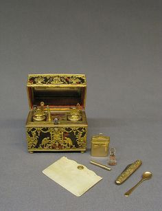 Nécessaire, 1st qrt18th century, German, Wood veneered with tortoiseshell & gold; implements of glass, ivory, & gold. Fashionable nécessaires de poche (pocket necessaries) were small caskets made of precious materials & fitted with tiny implements for grooming, writing, or sewing. Beneath a mirror-lined cover, the interior of this casket contains an inkwell & sand shaker, pen, pencil, clasp knife, cut-glass seal, snuff spoon, ear spoon, bodkin, tweezers, file, 2-leaved ivory tablet, & patch…
