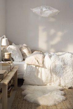 """Une chambre cocoon avec un dessus de lit en poil, un tapis en faux mouton et une suspension """"nuage"""" pour une ambiance hygge"""