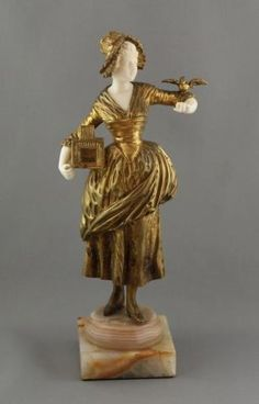 George Omerth Gilt Bronze and Ivory Figure, 1915. modeled as a young lady wearing bonnet and dress holding a bird cage under one arm and small bird resting on her other hand, signed in bronze, the whole on onyx base, h 25cm