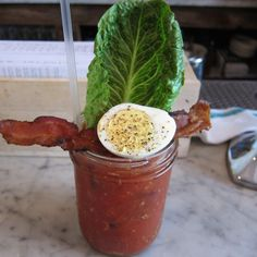 NYC's 14 Best Bloody Marys The Bloody Mary at NYC's Jacob's Pickles is a piece of art, assuming your idea of art involves topping things with eggs and bacon. It's served in a Mason jar, garnished with a fresh stalk of romaine lettuce, that strip of bacon we talked about, and half a hard-boiled egg with salt and pepper.