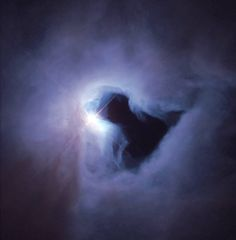 Cloud of dust and gas in purple with bright light behind and dark space resembling street lamp in center