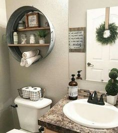 Galvanized wash tub shelf idea over the toilet. Black wire basket to hold toilet paper on top of the toilet, faux granite counter top and orb painted faucet,  great diy bathroom remodel inspiration and decor ideas for builder grade bathrooms!