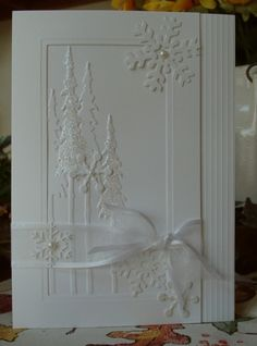 white on white card ... start with embossing floler trees ... add glitter pears and organza ribbon ... create a die cut frame ... decorate it with some scoring and a snowflake ... end up with a gorgeous winter card ...