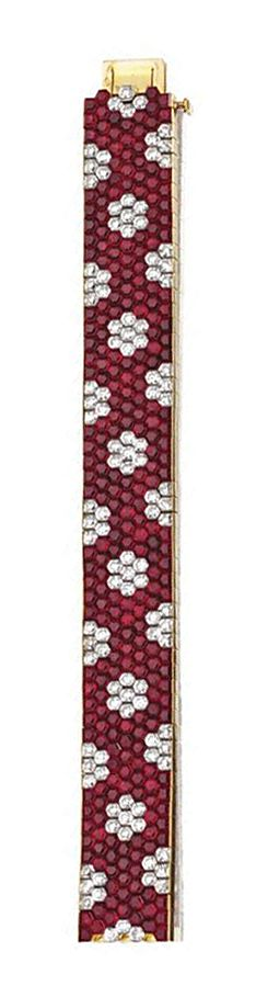 MYSTERY-SET RUBY AND DIAMOND BRACELET, VAN CLEEF & ARPELS, PARIS.  The flexible band mystery-set with a pattern of florets of hexagonal-cut diamonds within a ground of hexagonal-cut rubies, mounted in 18 karat gold, length 7 inches, signed VCA, numbered M39529, maker's mark, assay mark. With signed box.