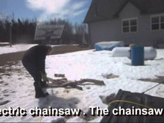 sawing firewood using the solar tonneau cover to power he electric chainsaw