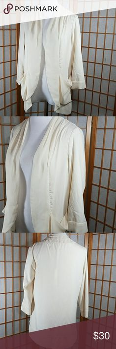 """Lauren Conrad open cream colored soft blouse LC Lauren Conrad, open cream colored soft blouse. Front pockets, no buttons. Wide lapels and soft flowy material. Size Medium measures approx 18"""" across from armpit to armpit when laid flat and 16"""" across the waist. 26"""" long from the top of the shoulder to hem  Brand new with tags. LC Lauren Conrad Tops Blouses"""