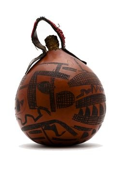 """Africa   Gourd container ~ """"a'untenakwete"""" ~ from the Hadza people of Lake Eyasi region, Tanzania   Gourd with leather handle that is decorated with red, blue and white glass beads.  The stopper is made from an ear of maize   These types of gourds were used to store animal fat.   ca. 1966"""